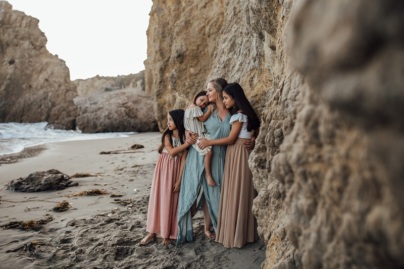 Sonoma Family Photography, mother standing against stone cliff side at beach with her daughters