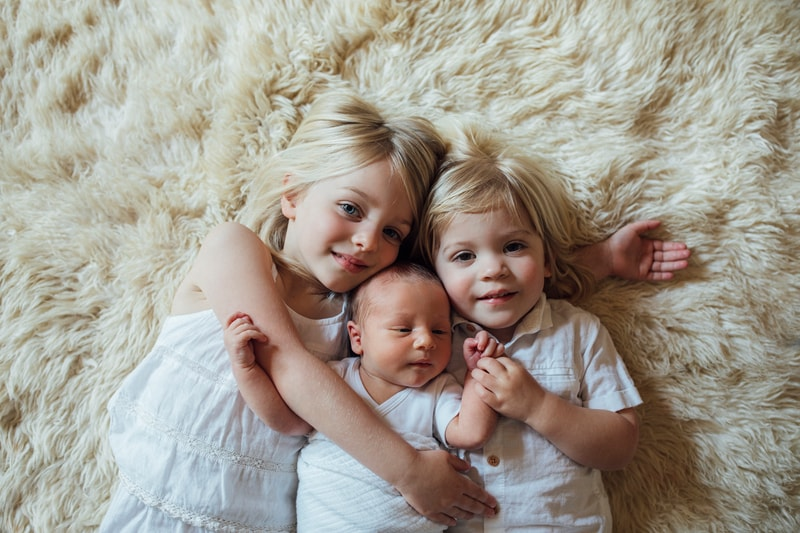 Sonoma Family Photography, two siblings laying on the ground next to their new baby