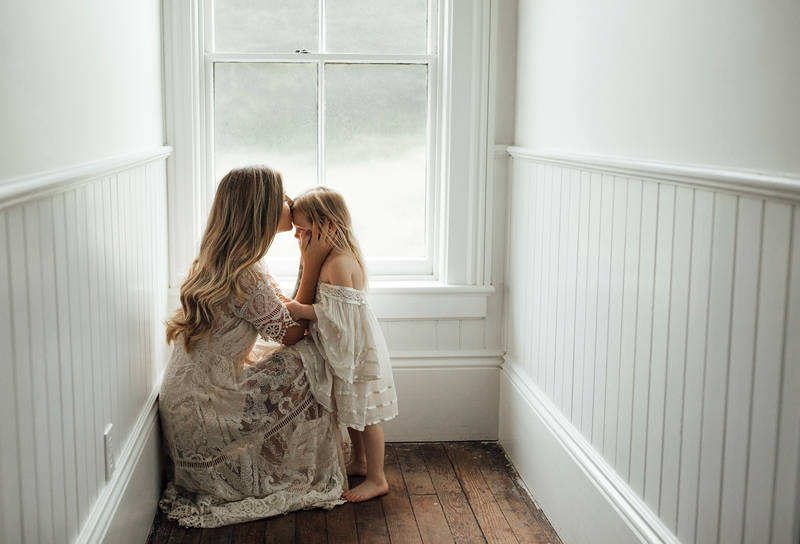 Sonoma Family Photography, mother kneeling down and kissing her child's forehead
