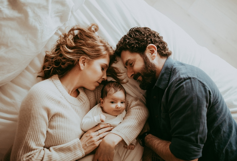 Sonoma Family Photography, couple laying with new baby