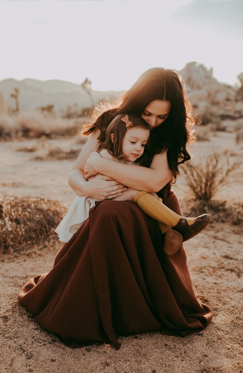 Sonoma Family Photography, mother sitting in the dessert holding daughter on her lap
