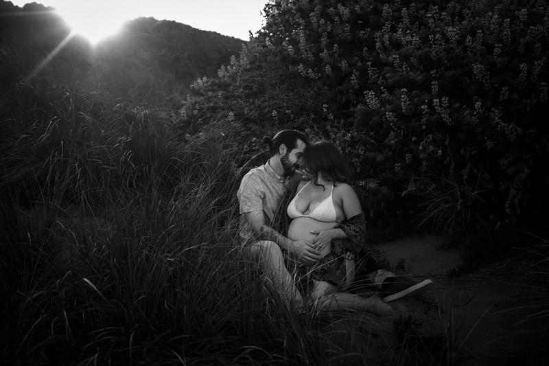 Sonoma Family Photography, man and pregnant woman sitting on the ground, holding each other