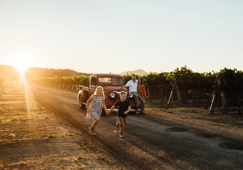 Sonoma Family Photography, family of four playing on old dirt road with truck in the background