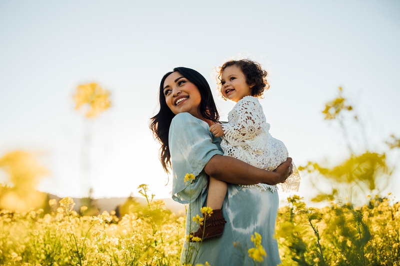 Sonoma Family Photography, mother in a field of flowers holding toddler around her pregnant belly