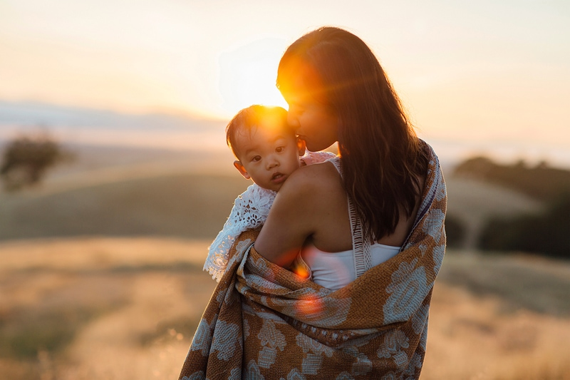 Sonoma Family Photography, little baby looking over their mom's shoulder with sunset in the background