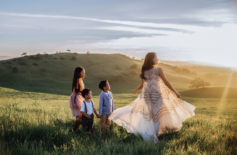 Sonoma Family Photography, mother twirling around a grassy hillside with her children